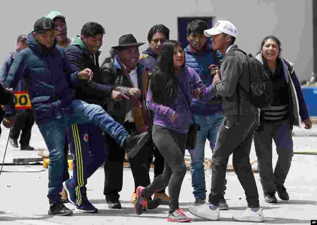 A woman is kicked by a member of a group of President Evo Morales' followers in La Paz, Bolivia.