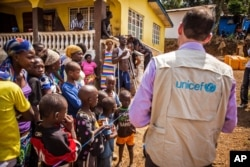 FILE - A UNICEF aid worker visits a home in Freetown, Sierra Leone.