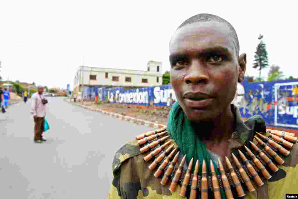 A M23 fighter, wearing a belt of ammunition, walks down a street in Goma, after the rebels captured the city from the government army, November 20, 2012.