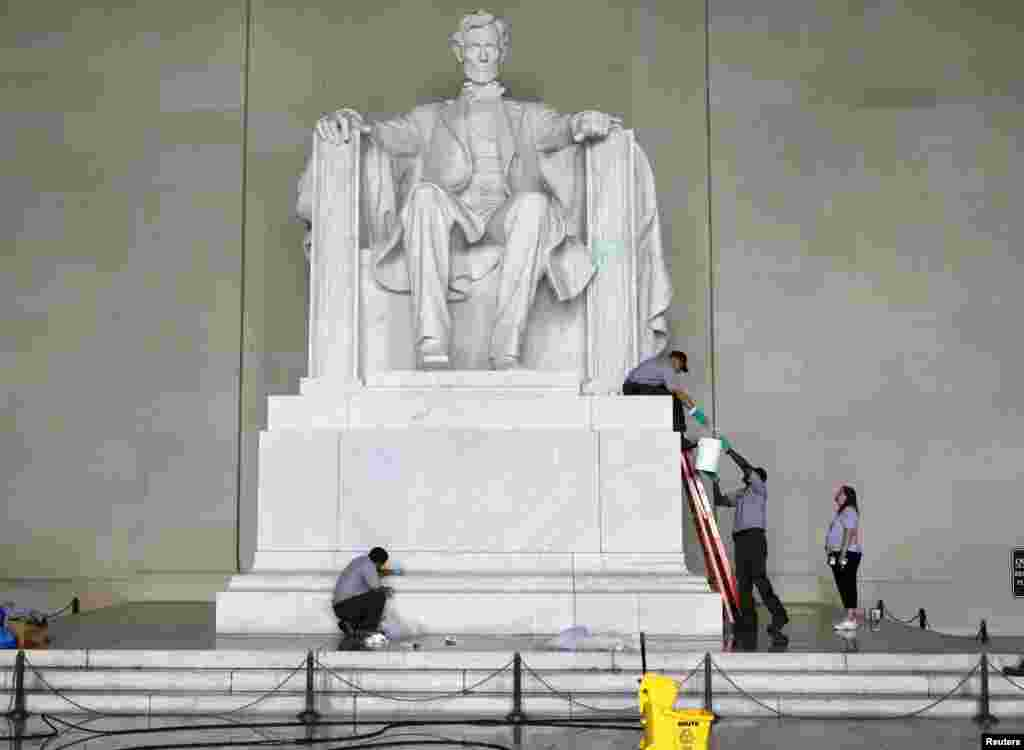 National Park Service employees clean green paint from the Lincoln Memorial in Washington, July 26, 2013.