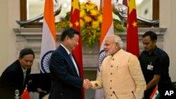 Presiden China Xi Jinping berjabat tangan dengan Perdana Menteri India, Narendra Modi, dalam pertemuan di New Delhi, September 2014. (AP/Manish Swarup)
