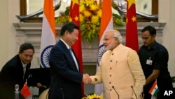 Presiden China Xi Jinping menjabat tangan PM India Narendra Modi (kanan) seusai penandatanganan kesepakatan di New Delhi, India (18/9).