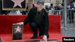 Ron Howard touches his star on the Hollywood Walk of Fame after being honored with the 2,568th star in Los Angeles, California, Dec. 10, 2015.