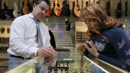 Roy Knudsen, a loan officer and salesman at Suffolk Jewelers & Pawnbrokers in Boston, shows earrings to a customer in November 2011