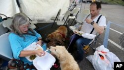 Evacuees Donna Herzog and her husband Richard Herzog, with their five dogs, eat food served by volunteers, in the aftermath of Tropical Storm Harvey, in a staging area as they wait for buses to go to evacuation shelters in Vidor, Texas, Sept. 1, 2017.