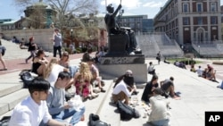 FILE - Students gather on the steps of Columbia University's Low Memorial Library next to Daniel Chester French's sculpture, Alma Mater, April 29, 2015 in New York. (AP Photo/Mark Lennihan)