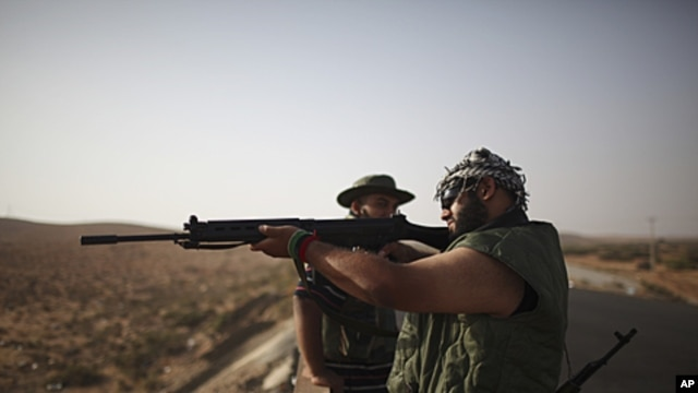 A rebel fighter checks a rifle at a checkpoint between Tarhouna and Bani Walid. Moammar Gadhafi is determined to fight his way back to power, the toppled dictator's spokesman said but a large convoy of his soldiers has apparently deserted, crossing the Li