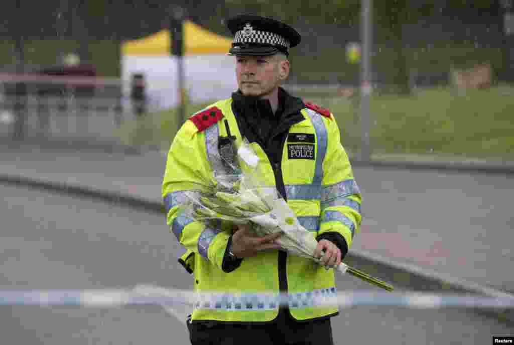 A police officer carries flowers near the scene of the killing of a British soldier in Woolwich, southeast London. The soldier was hacked to death on May 22, 2013, by two men shouting Islamic slogans.