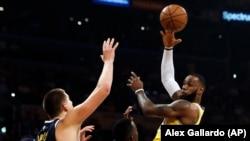 La vedette des Lakers et de la NBA, LeBron James, à droite, contre Nikola Jokic des Denver Nuggets, Los Angeles, Californie, le 25 octobre 2018.