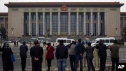 People watch as police officers check visitors in front of the Great Hall of the People during a gathering of the 205-member Central Committee's third annual plenum in Beijing, China, Nov. 9, 2013.