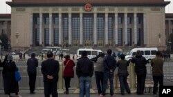 北京天安门广场上的人们观察警察在人民大会堂检查访问者(2013年11月9日)