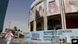 ຜູ້ຊາຍຄົນນຶ່ງຍ່າງຜ່ານຮູບພາບບັນດາຜູ້ນຳ Saudi Arabia ຢູ່ທີ່ ຕຶກກຳລັງກໍ່ສ້າງ ໃນນະຄອນ Riyadh ປະເທດ Saudi Arabia.