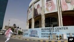 一名男子走过沙特阿拉伯利雅得一栋有沙特领导人头像的大楼(2016年4月19日)