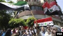 Demonstran anti-pemerintah Suriah mengibarkan bendera revolusi saat melakukan unjuk rasa di Kairo, Mesir (6/9).