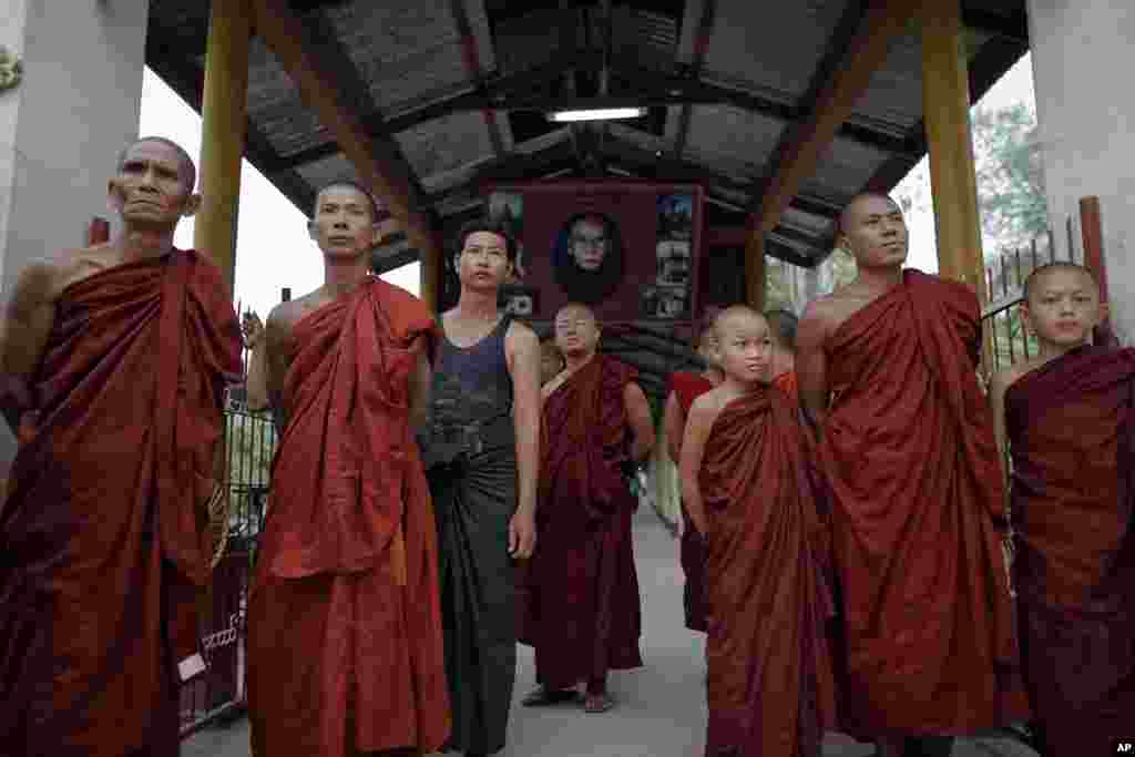 Buddhist monks try to get a glimpse of Aung San Suu Kyi visiting a polling station near their monastery in Kawhmu township, April 1, 2012. (Reuters)