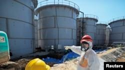 Menteri Ekonomy, Perdagangan dan Industri Jepang, Toshimitsu Motegi (kanan), mengenakan pakaian pelindung dan masker, meninjau tanki air yang terkontaminasi di PLTN Daiichi Fukushima (26/8). Tingkat radiasi di PLTN tersebut dilaporkan telah melonjak ke tingkat potensi bahaya hanya dalam waktu satu minggu, Sabtu (31/8).