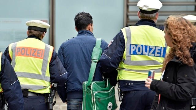 FILE - Police lead away a man at the main train station in Cologne, Germany, Jan. 12, 2016. New Year's Eve sexual assaults and robberies in Cologne were blamed largely on foreigners and pushed the discussion about the migration crisis.