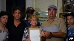 Ileana Yarza (76 tahun) bersama keluarganya di Havana, Kuba memegang surat yang diterimanya dari Presiden Obama (17/3).