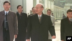FILE - Former South Korean President Chun Doo Hwan, center, leaves the Anyang Prison with his aides following his release from prison in a special amnesty, Dec. 22, 1997.