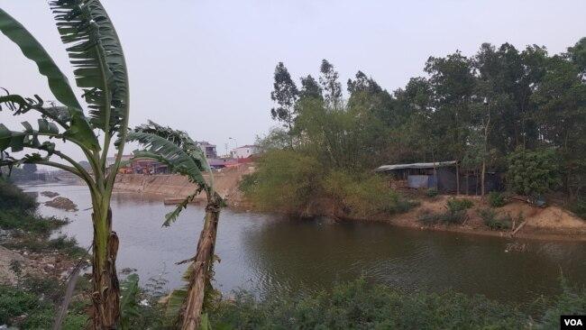 Cạnh khu vườn nhà anh Hiếu (phải) là khu vực dự án đã được san lấp, xây kè. Ngày trước, xung quanh khu vườn của anh là sông nước; nay lòng sông rộng 290m đã bị san lấp đến 4/5.
