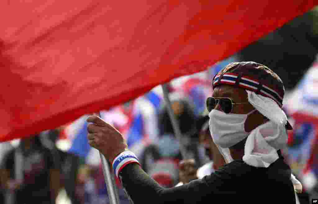 An anti-government protester waves a national flag during a rally in Bangkok, Feb. 7, 2014.
