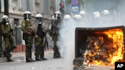 A fire burns as riot police look on during clashes with activists protesting German Chancellor Angela Merkel's visit in Athens, Greece, Oct. 9, 2012.