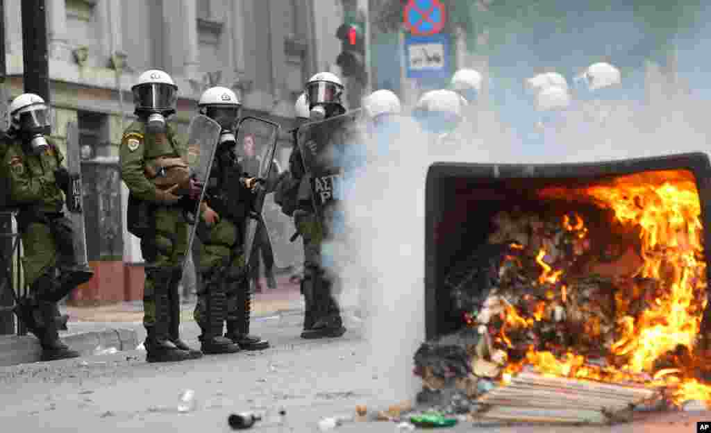 A garbage bin burns as riot police look on during clashes in front of the parliament in Athens, Greece, October 9, 2012.