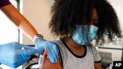 FILE - Jackson State University student Kendra Daye reacts as a nurse with the Jackson-Hinds Comprehensive Health Center injects her with the Pfizer COVID-19 vaccine, in Jackson, Miss., Sept. 21, 2021.