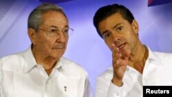 Cuba's President Raul Castro (L) talks with Mexico's President Enrique Pena Nieto during a news conference at the Yucatan State Government Palace in Merida, Mexico, Nov. 6, 2015.
