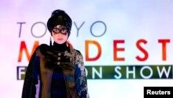 Seorang model memperagakan kreasi perancang mode Lynn Siregar dengan merknya Weddingku Gallery dalam Tokyo Modest Fashion Show, pagelaran mode Muslim, di Halal Expo Japan, Tokyo (22/11). (Reuters/Toru Hanai)
