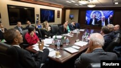 U.S. President Barack Obama, left, receives an update Wednesday in the Situation Room from Secretary of State John Kerry.