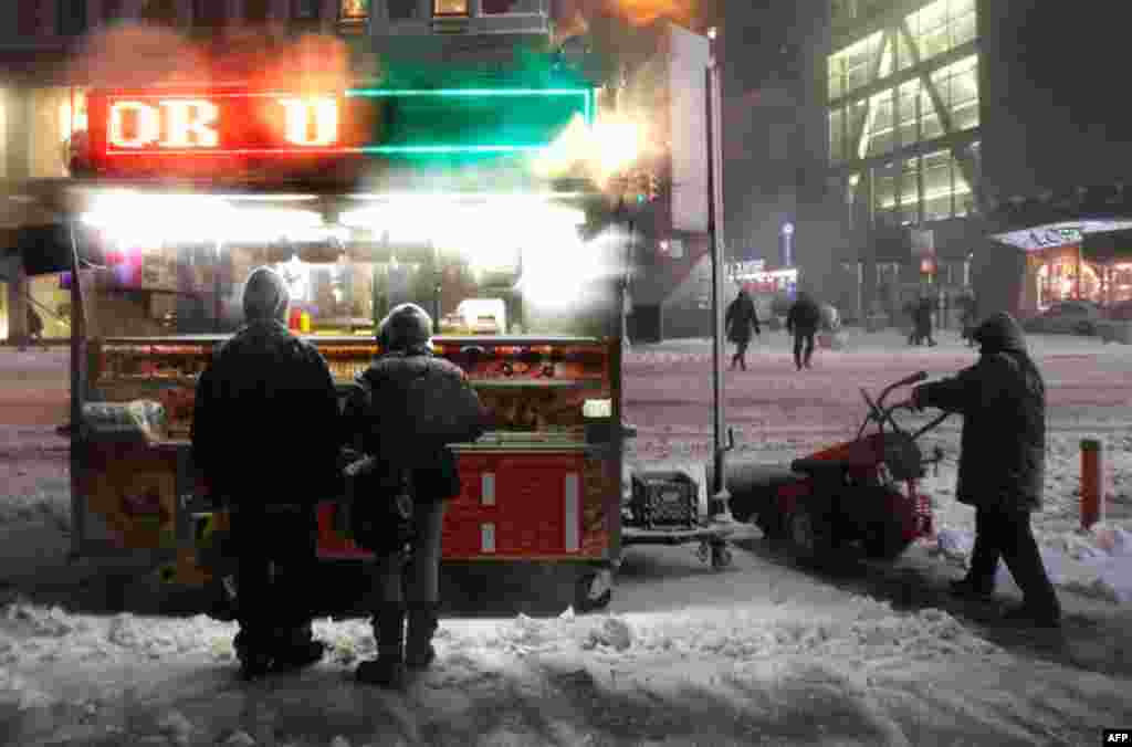 January 26: People wait to buy food from a stand as a man snowplows during a snowstorm in New York. (Reuters/Shannon Stapleton)