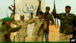 ຮູບຈາກໂທລະພາບ ຂອງທາງການລີເບຍ ໃນວັນທີ 11 ມີນາ 2011 ທີ່ສະແດງໃຫ້ເຫັນວ່າ ກຳລັງທີ່ຈົງຮັກພັກດີຕໍ່ຜູ້ນຳລີເບຍ ທ່ານ Moammar Gadhafi ພາກັນສະຫຼອງ ທີ່ເມືອງ Ras Lanuf ຫຼັງຈາກໄດ້ຂັບໄລ່ກຳລັງຕໍ່ຕ້ານອອກໄປຈາກເມືອງດັ່ງກ່າວ.