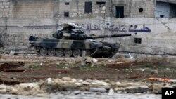 یک تانک ارتش سوریه در مقابل دیواری که روی آن نوشته شده، حلب پایتخت فرهنگ است.