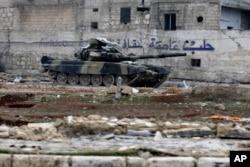 """ລົດຖັງທະຫານຊີເຣຍຄັນນຶ່ງ ເຫັນຢູ່ຕໍ່ໜ້າປ້າຍທີ່ຂຽນເປັນພາສາອາຣັບວ່າ """"Aleppo ເປັນເມືອງຫລວງວັດທະນາທຳ."""""""