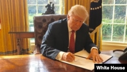White House Press Secretary Sean Spicer tweeted this photo of President Donald Trump signing a new executive order to ban travelers from six Muslim-majority nations on Mar. 6, 2017. The media was not invited to see the president signing the order.