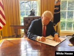 White House Press Secretary Sean Spicer tweeted this photo of President Donald Trump signing a new executive order to ban travelers from six Muslim-majority nations on Mar. 6, 2017.