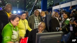 FILE - Deputy President Cyril Ramaphosa, seated, and African National Congress party members discuss municipal election results at the results center in Pretoria, South Africa, Aug. 5, 2016.