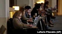 In this photo taken Wednesday, April 3, 2013, people work on their computers at the British Library in London.