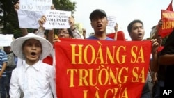 "Vietnamese protesters carry a banner with a Vietnamese slogan reading, ""Paracel islands and Spratly islands belong to Vietnam,"" during a protest demanding China to stay out of their waters following China's increased activities around the Spratly Islands"