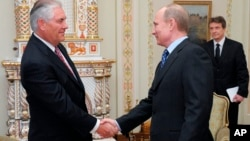FILE - Vladimir Putin (R), then Russia's prime minister, shakes hands with Rex Tillerson, chairman and chief executive officer of Exxon Mobil Corporation, at their meeting at the Novo-Ogaryovo residence outside Moscow, April 16, 2012.