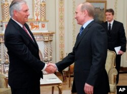 FILE - Russian Prime Minister Vladimir Putin, right, shakes hands with Rex Tillerson, chairman and chief executive officer of Exxon Mobil Corporation, at their meeting outside Moscow, April 16, 2012.
