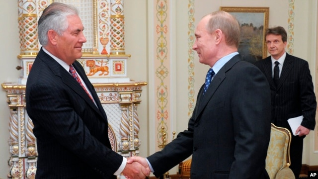 FILE - Russian Prime Minister Vladimir Putin, right, shakes hands with Rex W. Tillerson, chairman and chief executive officer of Exxon Mobil Corporation at their meeting in the in 2012.
