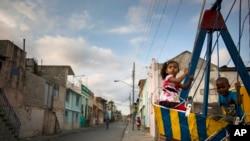 FILE - Children play on a swing in Santiago, Cuba, March 21, 2015.