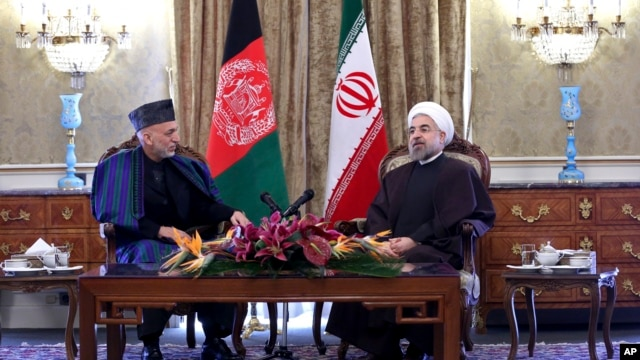 Iran's President Hassan Rouhani (R) speaks with Afghan President Hamid Karzai during their meeting at Tehran's Saadabad Palace Dec. 8, 2013.