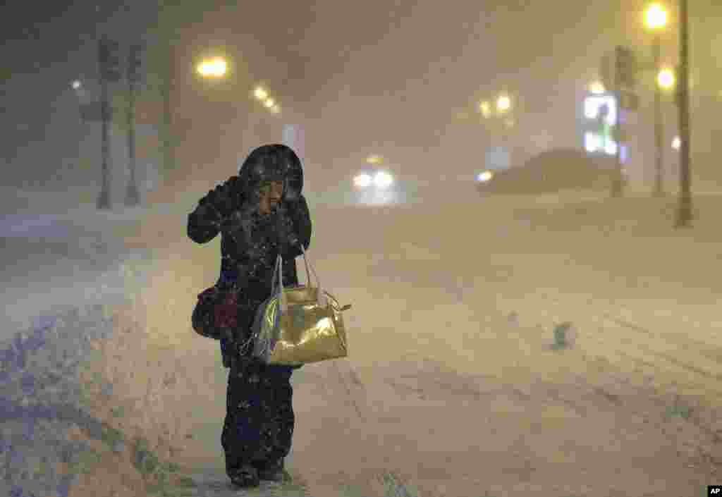 Denise Young of Lynnfield, a nursing supervisor at Massachusetts General Hospital, adjusts her hood while walking to work in Boston. A storm packing blizzard conditions spun up the East Coast, pounding coastal eastern Long Island into Maine with high winds and heavy snow.