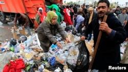 Des manifestants aident les travailleurs de la municipalité à débarrasser des tas d'ordures devant le bureau du Premier ministre à la Kasbah, la vieille ville de Tunis, le 27 janvier 2011