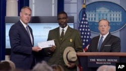 Interior Secretary Ryan Zinke, left, and Harpers Ferry National Historic Park Superintendent Tyrone Brandyburg, accompanied by White House press secretary Sean Spicer, hold up a check during the daily briefing at the White House in Washington, April 3, 2017.
