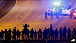 노스캐롤라이나주 샬럿에서 흑인 남성이 경찰 총격으로 숨진 데 항의하는 시위대가 23일 사건 현장 인근의 277번 고속도로를 점거한 채 진압 경찰과 대치하고 있다.