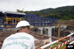FILE - A Lao worker rests near to the Nam Theun 2 power dam's powerhouse under construction 28 June 2007 in Laos' Nakai plateau.